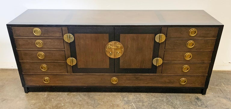 This buffet is absolutely stunning! This ebonized mahogany and walnut sideboard / buffet designed by Edward Wormley for Dunbar features heavy brass accents and pulls in a gorgeous chinoiserie feel.  A piece like this is so elegant and clean it can