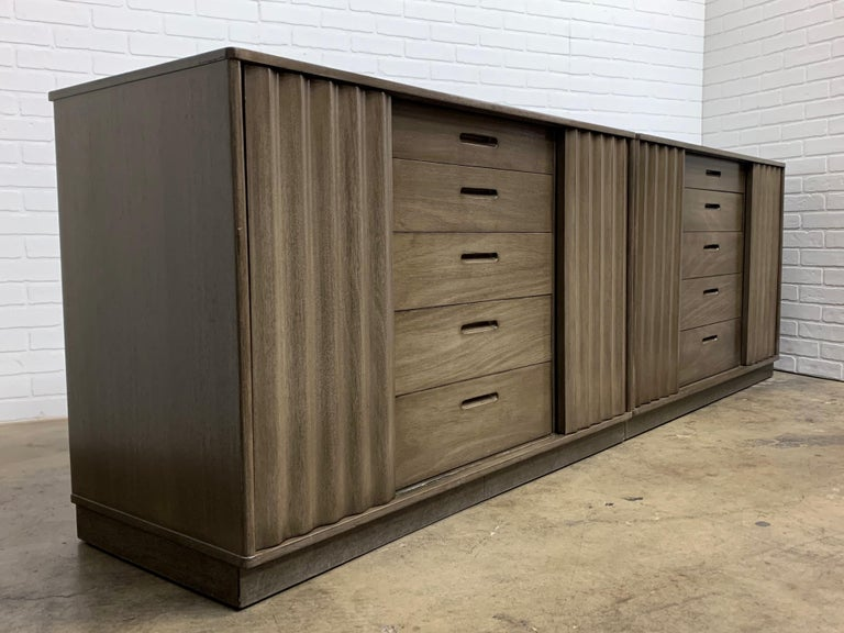 Two Edward Wormley cabinets with corrugated wood sliding doors and center drawer section in a grey brown finish Each cabinet is 20