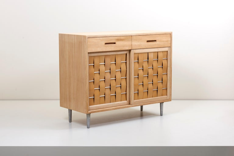 Elegant design by Edward Wormley for Dunbar Furniture Company, Berne Indiana. Perfectly refinished case with two top drawers and sliding woven front doors on metal legs. Fitted interior comprises six drawers.