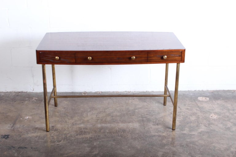 An oak and ash desk with brass base and hardware. Designed by Edward Wormley for Dunbar.