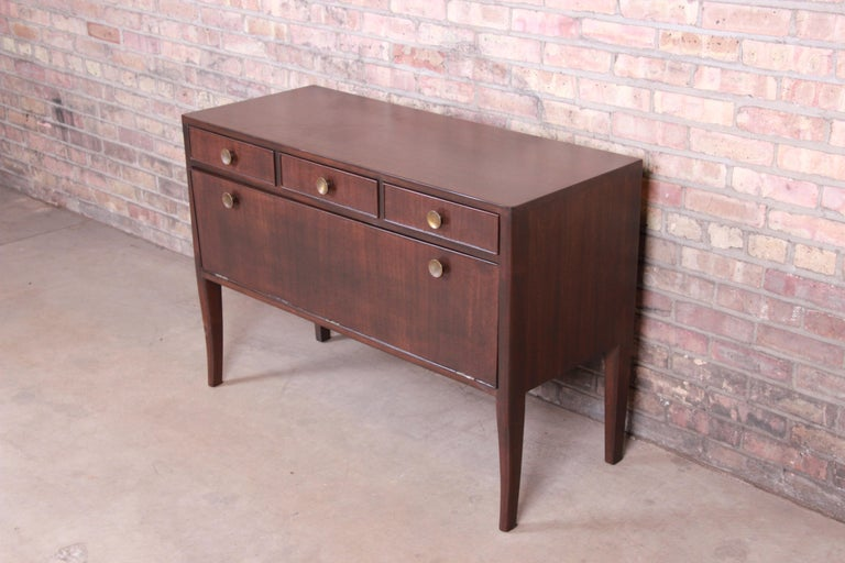 A stunning Mid-Century Modern sideboard credenza or bar cabinet  By Edward Wormley for Dunbar Furniture  USA, 1940s  Mahogany, with original brass hardware.  Measures: 43.38