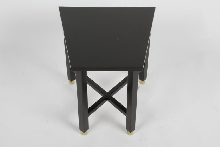 Newly refinished Edward Wormley for Dunbar Mid-Century Modern mahogany Trapezoidal end, drinks or side table in dark ebony with cross stretchers on round brass sabots. Marked with