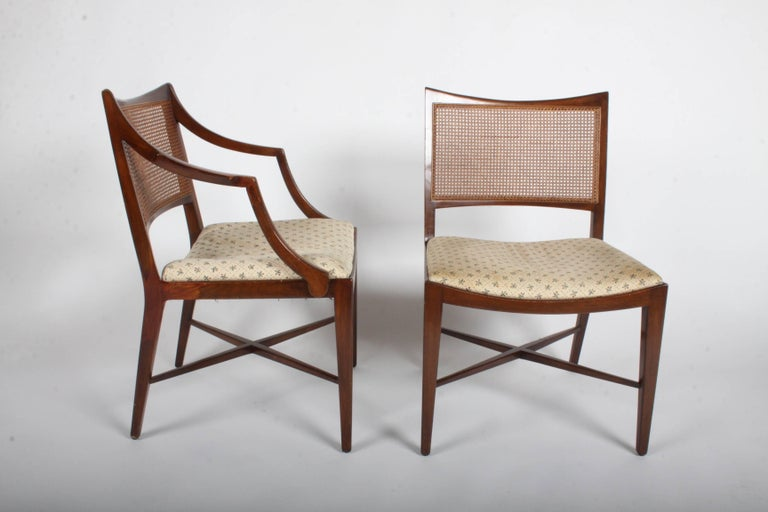 Elegant set of four Edward Wormley for Dunbar walnut frame and caned back dining chairs, two arms and two sides chairs. Curved back with caned panel and X-stretcher on legs. Includes frames to be refinished prior to shipping, seats are need of