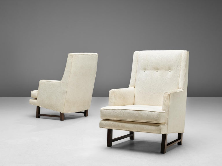 Edward Wormley for Dunbar, pair of lounge chairs, fabric and mahogany, United States, 1950s  These comfortable high back chairs are designed by Edward Wormley in the 1950s. It has straight lines and a basic wooden frame, yet some classic elements