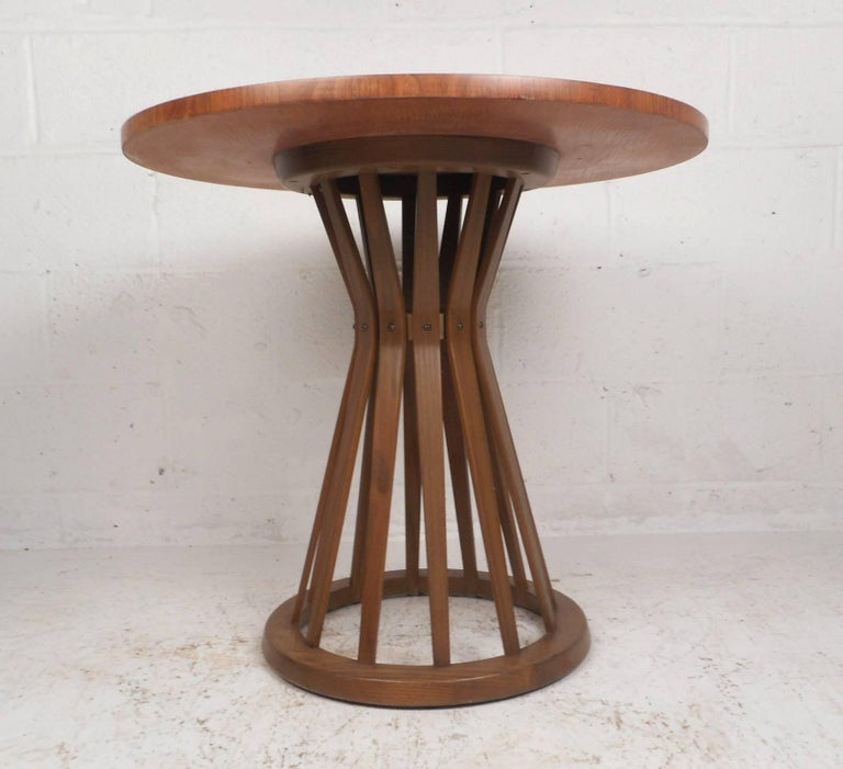 This iconic Mid-Century Modern side table by Edward Wormley features a gorgeous round top with walnut wood grain. This unique piece has an hourglass shaped base with spindles tapering down to a circular bottom. This stylish vintage modern end table
