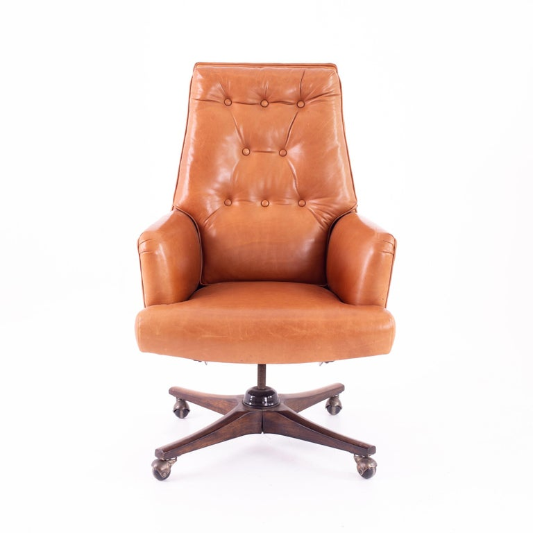 Edward Wormley for Dunbar style Mid Century leather orange desk chair Chair measures: 27 wide x 25 deep x 44 high with a seat height of 19 inches  This piece is available in what we call restored vintage condition. Upon purchase it is thoroughly