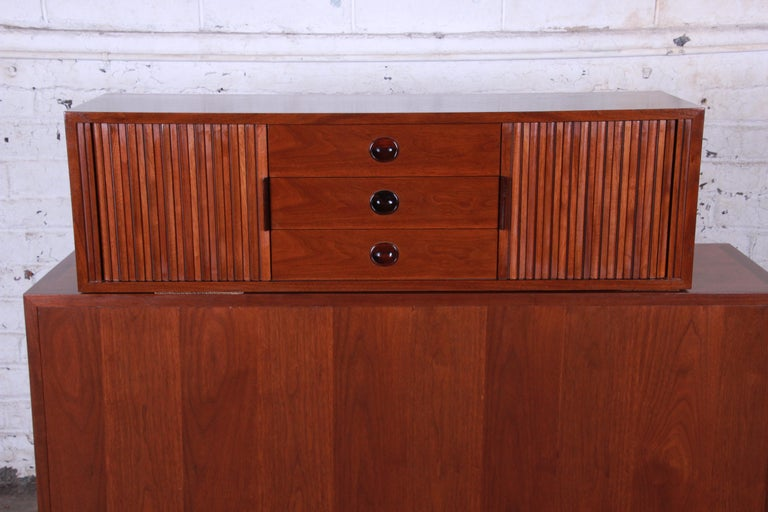 A rare and exceptional Mid-Century Modern tambour door walnut floating wall-hanging credenza designed by Edward Wormley for Dunbar. The credenza features gorgeous walnut wood grain and sleek Danish-inspired midcentury design. It offers good storage,
