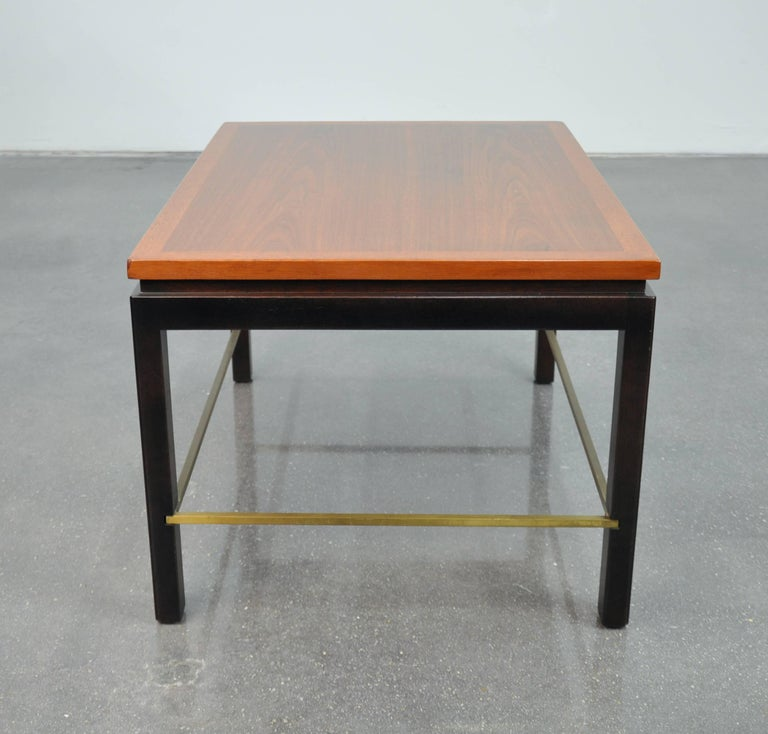 A vintage Mid-Century Modern model 310 end or occasional table designed by Ed Wormley for Dunbar and dating from the 1950s. The rectangular top appears to float over a recessed Parsons style ebonized mahogany base connected with inset brass