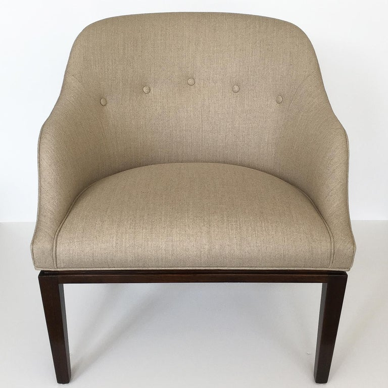 Sophisticated and tailored lounge chair by Edward Wormley for Dunbar, circa 1950s. Dark mahogany base with inset reveal just below the upholstery line. Curved back with splayed angled legs. Newly upholstered in a heathered natural oatmeal colored