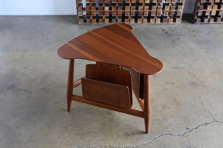 Edward Wormley magazine table model 5313. Manufactured by Dunbar, circa 1953. This table retains the original Dunbar tag to the bottom. This piece has been professionally restored.