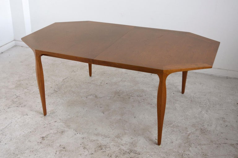 A beautiful example of Ed Wormley's refined aesthetic and Dunbar's quality construction, this dining table has a very pleasing mix of straight lines and elegant curves. The octagonal top has a skirt and legs with undulating lines. The top also has