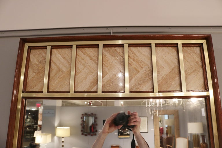 A modernist mirror designed by Edward Wormley. Mahogany with patinated brass trim details with seven panels of travertine inset into the top of the mirror.