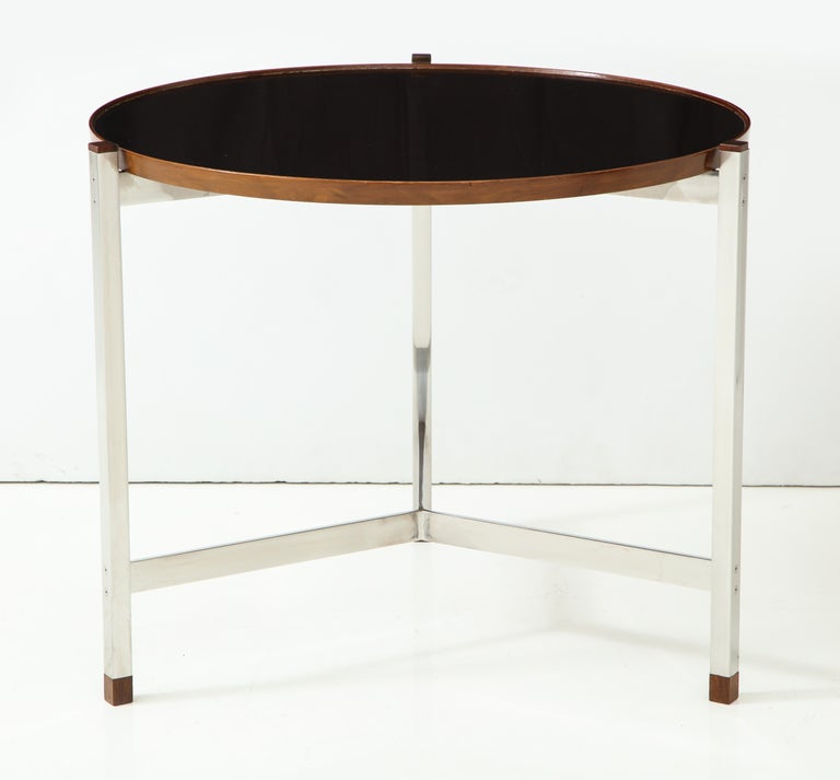 Round, rather large-scaled occasional table with a chromed steel three-leg base with flat cross stretchers and a top of black micarta with a walnut edge. Excellent proportions and details, including original set screws and Macassar ebony caps and