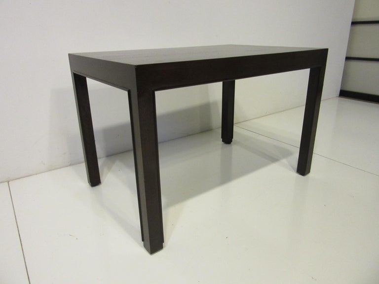 A nice sized side table in an ebony toned finish with detailed beading to the edge of each leg and retaining the gold metal big D tag and paper order label from the manufacturer designed by Edward Wormley for the Dunbar Furniture Company.