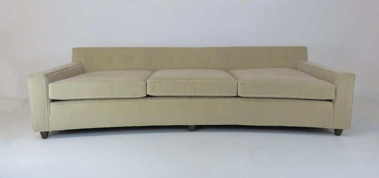 A wide, curved sofa by Edward Wormley sofa for Dunbar. Upholstered in a beige mohair.