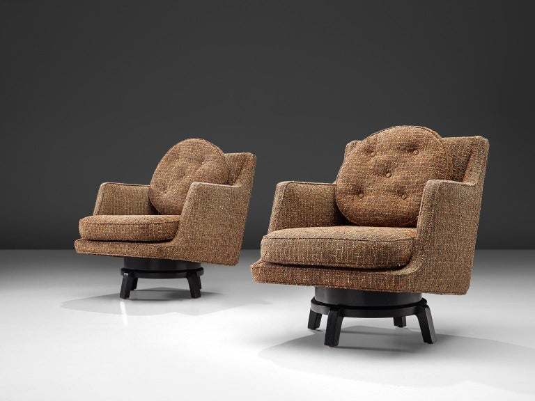 Edward Wormley, swivel lounge chairs model 5609, fabric, mahogany, United States, 1950s  These lounge chairs by Edward Wormley feature are a combination of a traditional designed seat with a wooden base that holds more playful aesthetics. The