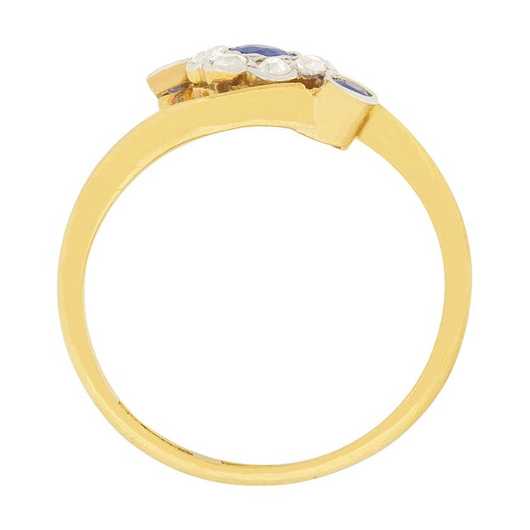 This lovely Edwardian ring features a daisy held within a gently twisting band. The daisy holds a 0.15 carat blue sapphire in the centre, which is surrounded by eight 0.03 carat old cut diamonds. They are H in colour and VS2 in clarity. Two