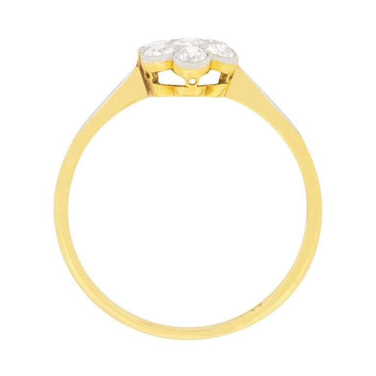 This sweet Edwardian daisy ring is adorned with old cut diamonds. The centre diamond is 0.08 carat, and the surrounding diamonds are 0.07 carat each. The diamonds match for quality, with colour grades of F and clarity grades of VS. They are set in