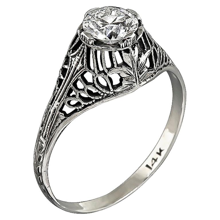 This elegant handmade 14k white gold engagement ring from the Edwardian era is centered with a sparkling round cut diamond that weighs 0.51ct. graded G with VS1 clarity. The ring is stamped 14K and weighs 1.4 gram. It is currently size 6 3/4, and