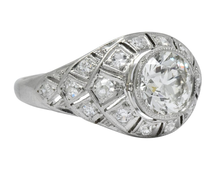Millegrain bezel setting centering a round brilliant cut diamond weighing 1.14 carats, K color and VVS1 clarity  Surrounded by a pierced and tiered geometric motif, prong set with Swiss cut diamonds weighing approximately 0.26 carat total, H/I color