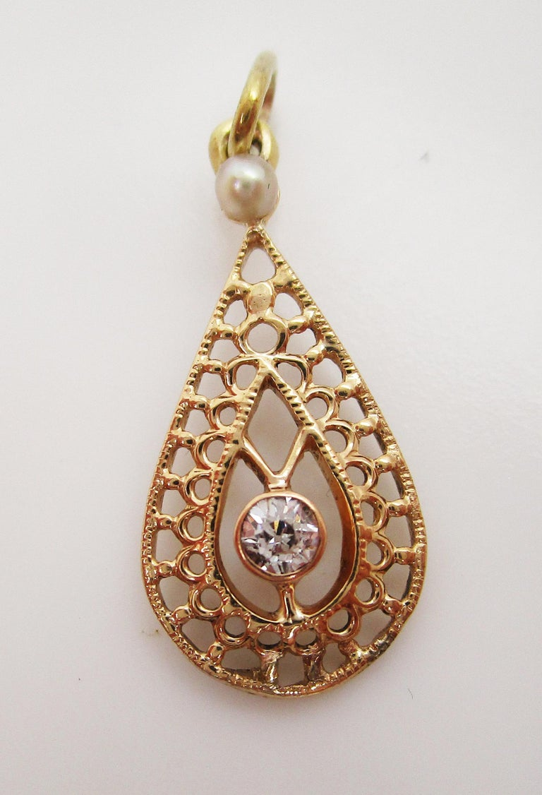 This lovely Edwardian pendant is in 14k yellow gold and features both a seed pearl and delicate diamond accent in an open pear design! The open design of the pendant creates a lacy look that is delicate and beautiful! At the top of the pendant sits