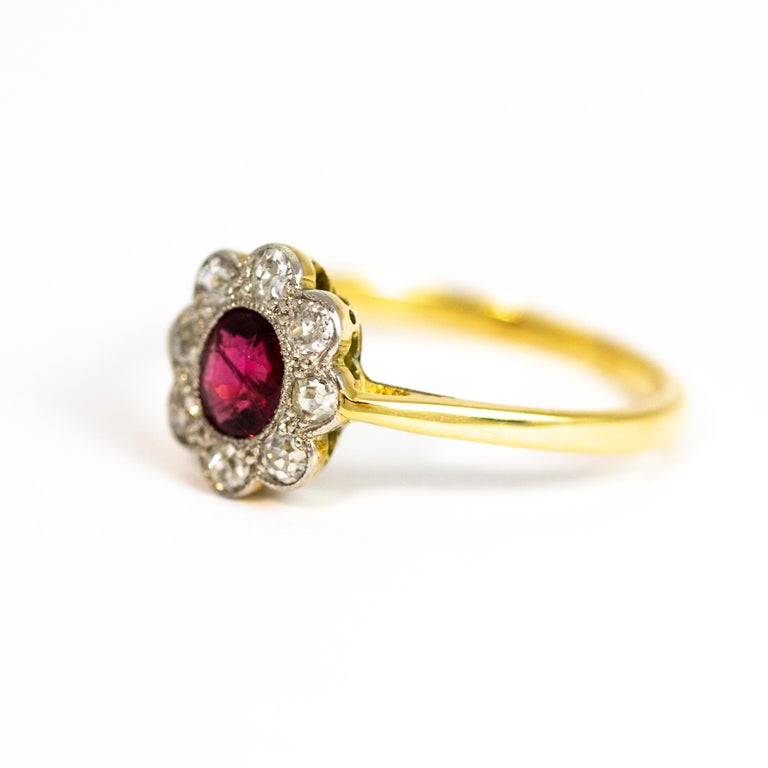 A wonderful antique Edwardian ruby and diamond cluster ring. Centrally set with a stunning red ruby surrounded by a halo of eight old European cut diamonds. The stones are set in platinum to enhance their colour. Band modelled in 18 carat yellow