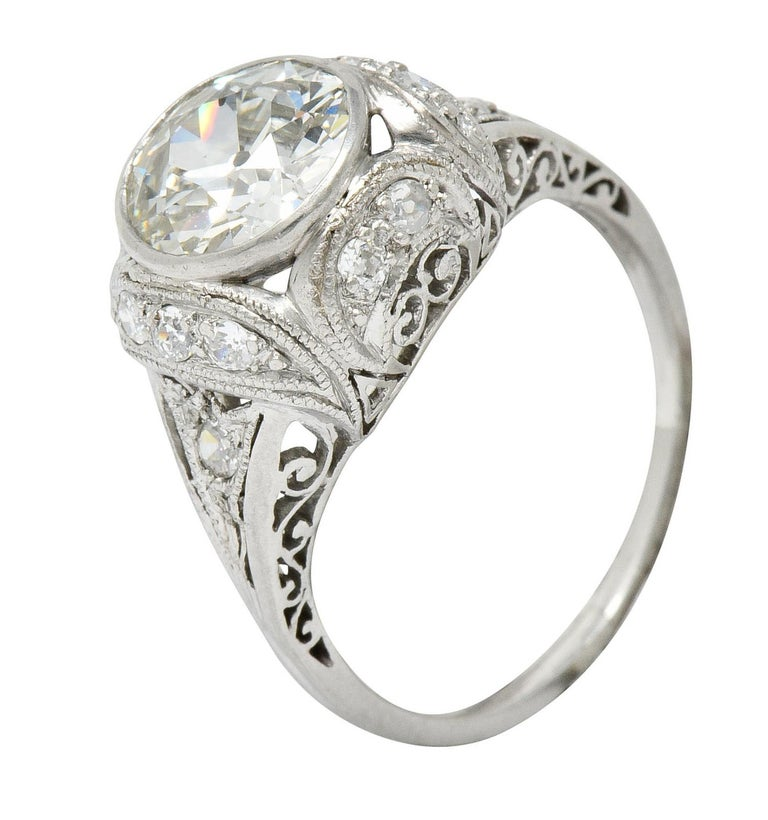 Centering a bezel set old European cut diamond weighing 1.73 carats; K color with SI1 clarity With a cushioned surround, filigree gallery, and pointed shoulders  Accented by old European cut diamonds weighing approximately 0.32 carats; eye-clean and
