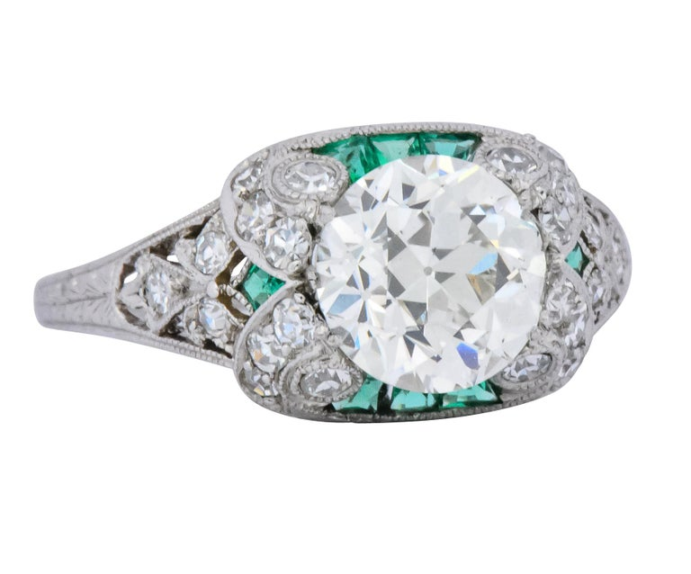 Centering an old European cut diamond weighing 1.59 carats, J color and SI1 clarity  With vibrant calibré french cut emeralds, channel set, tucked under the center  Accented by single cut diamonds weighing approximately 0.51 carats total, H color