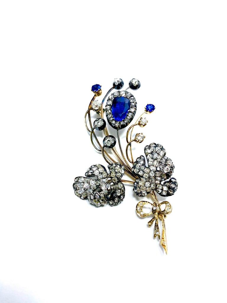 This is a gorgeous one of a kind Edwardian era Sapphire and Diamond silver over gold floral bouquet brooch.  The main royal blue pear shape Sapphire is 3.02 carats, accompanied by two round Sapphires totaling 0.40 carts.  The floral design contains