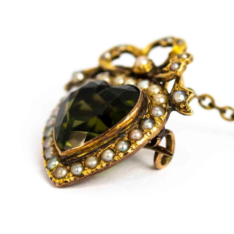 A superb antique Edwardian heart brooch. Centrally set with a heart-cut dark green paste surrounded by beautiful seed pearls. The brooch is topped with a beautiful bow motif inlaid with seed pearls. Modelled in 9 carat yellow gold.  Dimensions: 35mm