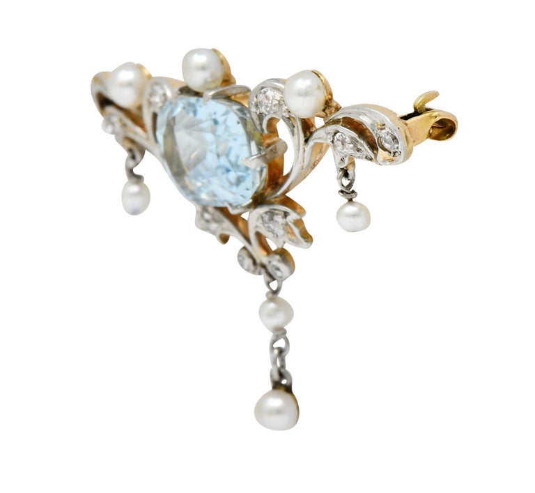 Centering a cushion cut aquamarine measuring approximately 11.0 x 7.5 mm; light blue  Surrounded by scrolling platinum foliate accented by old single cut diamonds  Weighing in total approximately 0.25 carat with I to K color and SI clarity  Accented