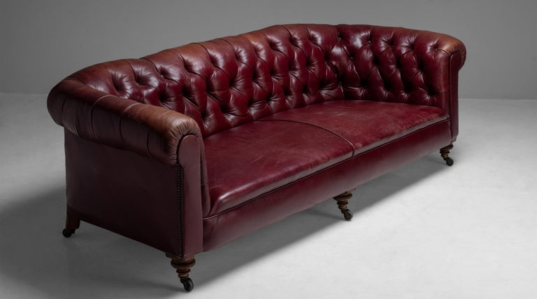 """Edwardian Chesterfield sofa England circa 1890 Deep button back Chesterfield with original red leather upholstery on turned feet with castors. Measures: 90.75""""W x 40""""D x 28.5"""" H  $ 9,500."""