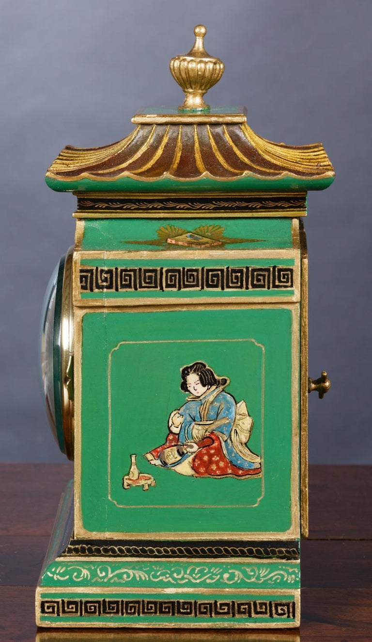 Mappin and Webb  Edwardian mantel clock housed in a chinoiserie decorated case on a green ground with typical Chinese scenes standing on a raised, stepped base and surmounted by a pagoda top with vase finial.  Eight day movement with lever