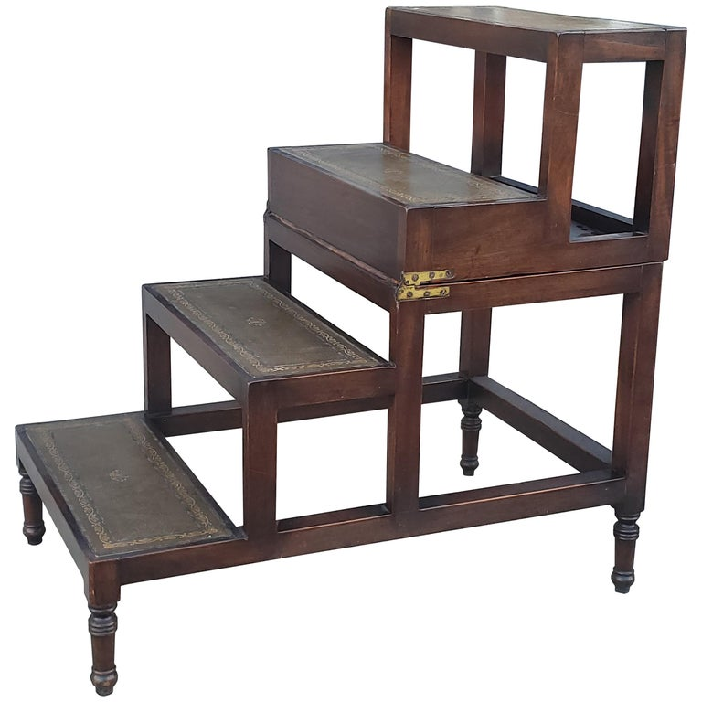 A George III design, mahogany four-step metamorphic library coffee table, with a naturally aged decorative gilt incised leather top and leathered steps opening to form a library step ladder on brass castors. Measurements are as stairs, table height