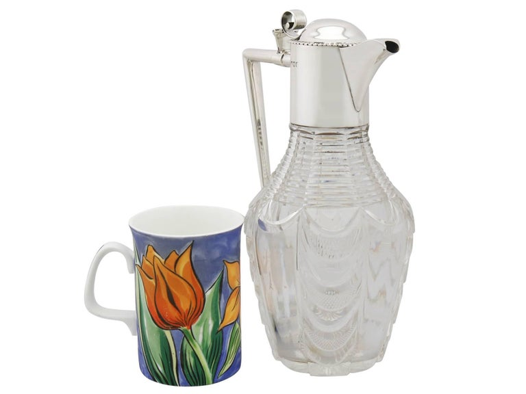 An exceptional, fine and impressive antique Edwardian cut glass and English sterling silver mounted claret jug; part of our wine jug collection.  This exceptional antique glass claret jug has a tapering circular shaped form.  The neck of the