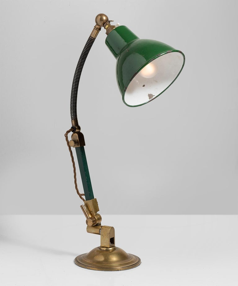 Original green enamel shade on flexible stem with turned brass base.