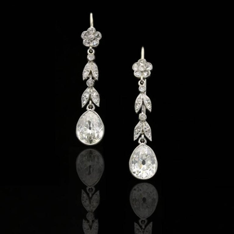 A beautiful pair of Edwardian diamond and platinum earrings, c.1910, each designed as a floral and foliate articulated drop set with rose cut diamonds suspending a single pear shaped old-cut diamond, all in platinum with millegrain details, to later