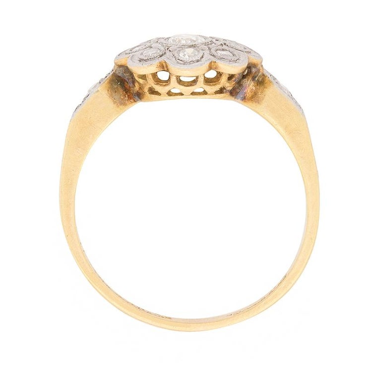 Dating to 1910, this Edwardian daisy cluster ring is a delicate and sweet ring. It features a total of 0.30 carat's worth of 8-cut diamonds, which are grain set within the flower design. The metal work shows off the craftsmanship of the piece, with