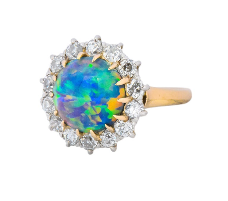 Centering a round cabochon opal, measuring 9.99 - 10.0 x 4.49 mm, translucent, with natural color and no indications of treatment  Excellent play-of-color in the green, blue, violet, yellow and orange spectrum, with a