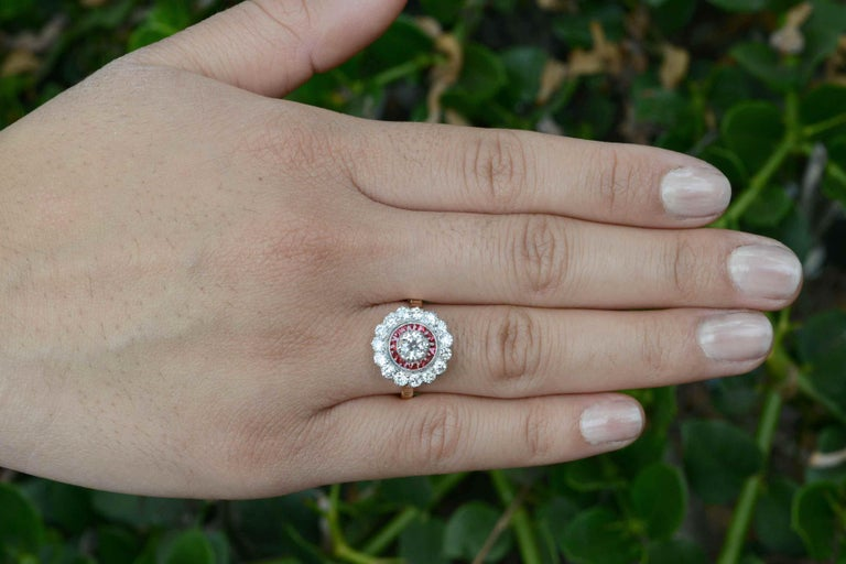 Centering on a bright and fiery old European cut 1/2 carat diamond, the alluring ruby flower cluster is so feminine. The sought after halo design is accented with French cut calibre' natural rubies  of a rich, vibrant red. This is an original