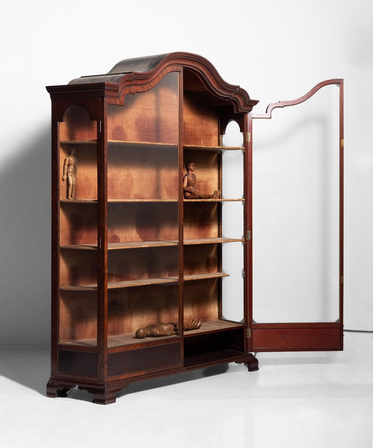 Elegant glass display cabinet with floating shelves and original velvet interior.