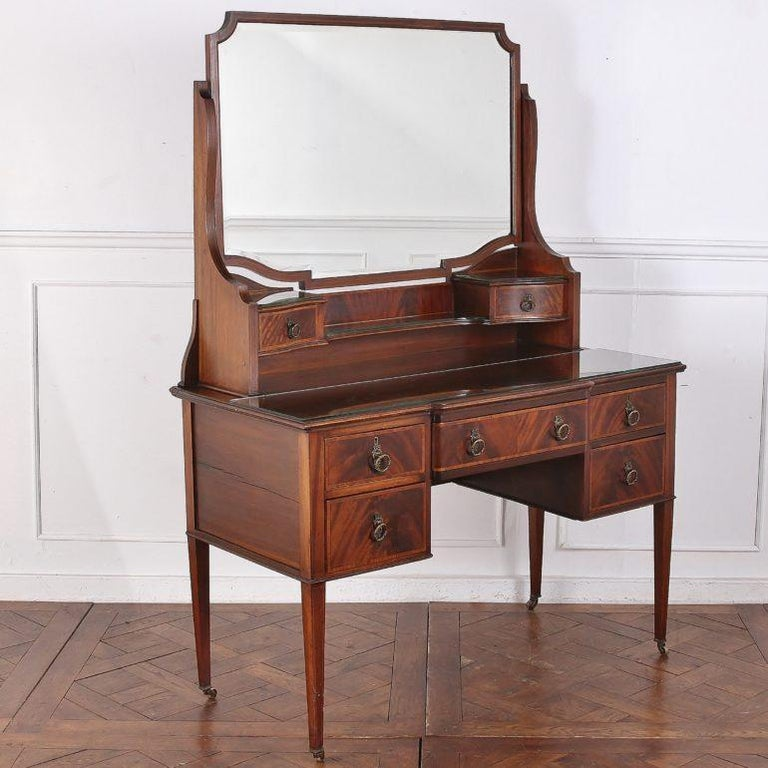 English, solid mahogany inlaid Edwardian vanity and mirror, with original brass drawer pulls and casters.