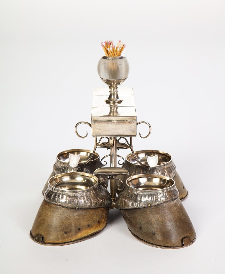 A stately Edwardian antique smoking compendium made circa 1908 by Robert Pringle & Sons. Four sterling silver ashtrays are set into four antique hooves. Mounted above are four graceful silver trays curved to rest a cigarette. The silver compartment
