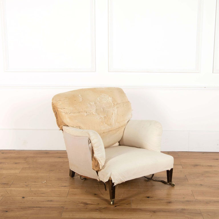 An Edwardian Howard Bridgewater armchair, standing on mahogany square tapering front legs. (For reupholstery).