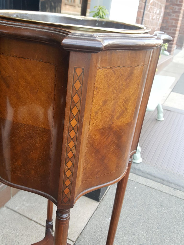 Edwardian inlaid mahogany plant stand, with brass liner, of serpentine outline and raised on down swept legs united by a shaped gallery 16.5