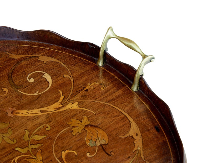 Good quality Edwardian tray, circa 1905.  Very much on par with the quality of inlay by Edwards and Roberts. Scalloped outer edge, with beautifully inlaid surface. Fitted with decorative brass handles.  Areas of restoration to wood work.
