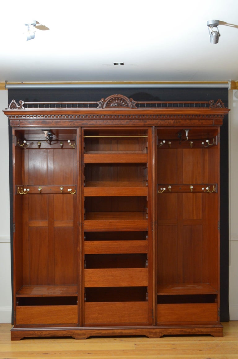 Sn4736, exceptional quality Edwardian wardrobe in mahogany, the cornice having carved centre flanked by spindles and shell carved corners over dentil decoration, all above mirrored centre door retaining original bevelled edge mirror and enclosing
