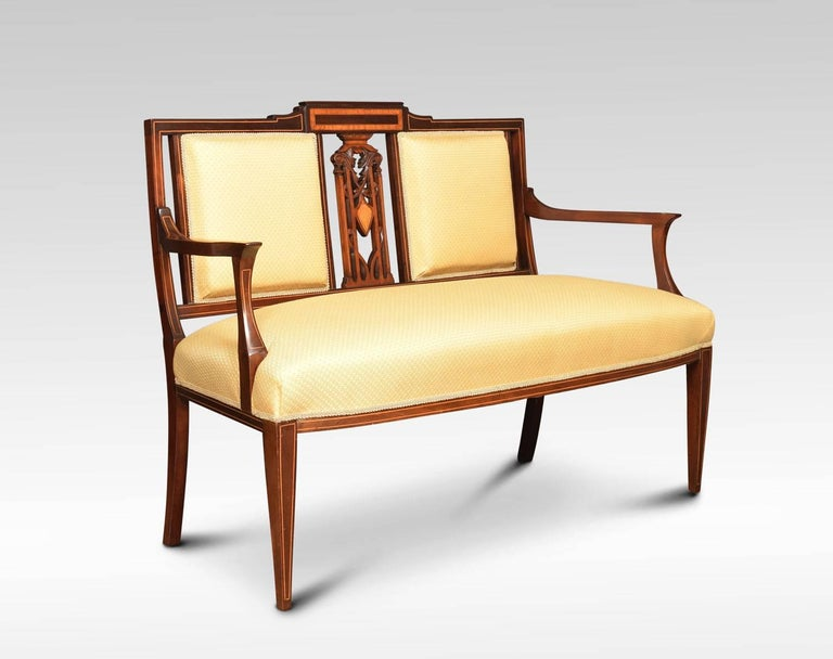 Edwardian mahogany and satinwood inlaid settee, with twin upholstered back panels flanking an intricate pierced splat. The upholstered seat flanked by out swept arms. All raised up on strung square tapering legs. Measure: Height 35.5 inches height