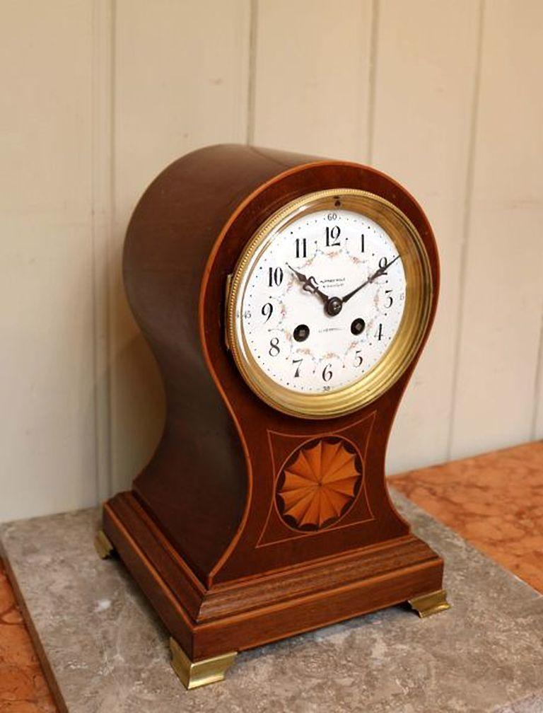 Edwardian mahogany balloon clock having boxwood stringing and a satinwood inlaid motif to the front with a floral hand decorated dial and an eight day gong striking movement made by Marti & Co raised on brass ogee feet.