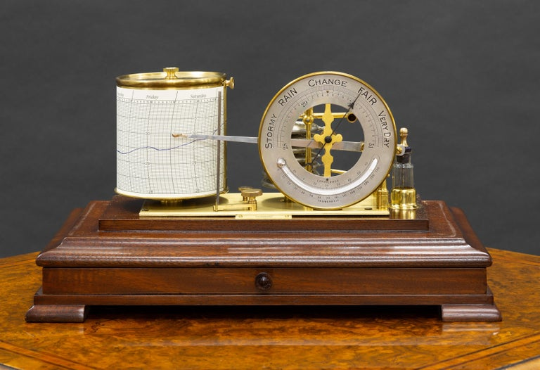 Edwardian mahogany barograph housed in a bevelled glass display case standing on a raised, moulded plinth and resting on four pad feet.  Seven vacuum Chambers upon the brass plate linking the pen arm to the revolving drum and linked to the